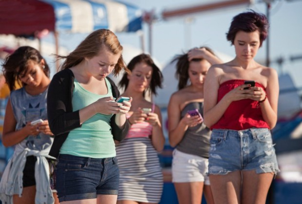 A group of teenage girls who are all on their smart phones