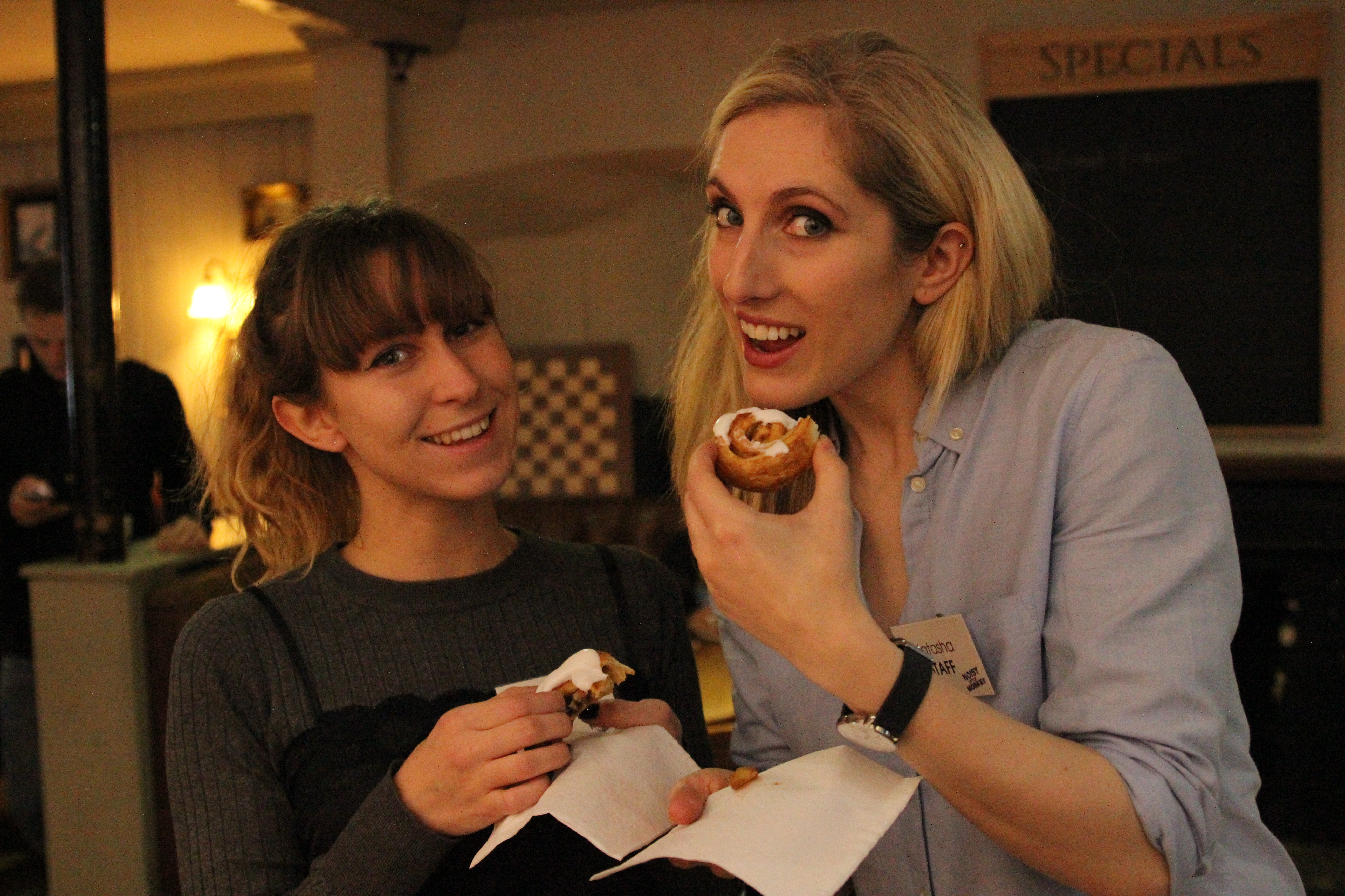 Claire and Natasha smiling and posing with their breakfast pastries