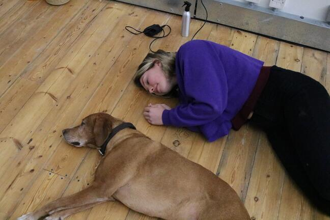 woman lying on floor with dog