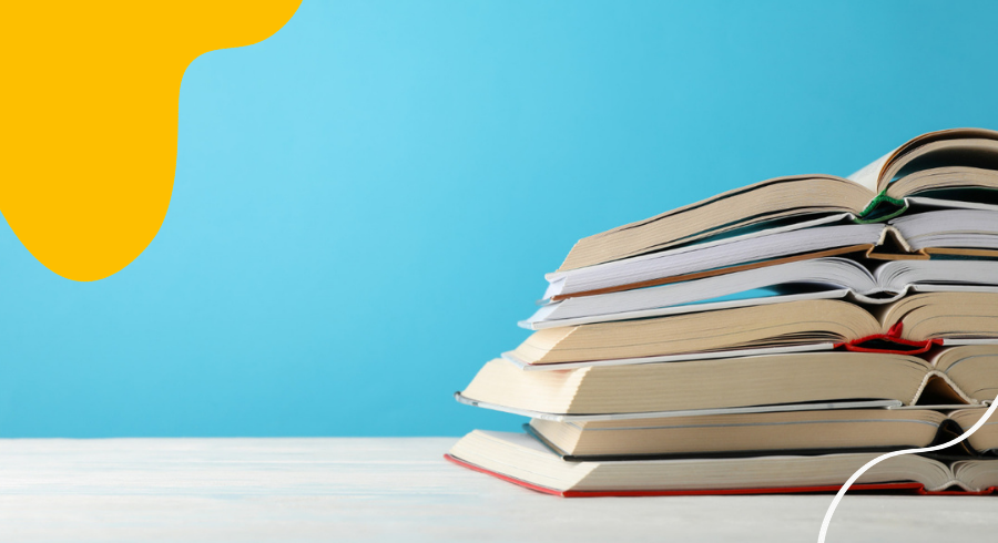This image shows a pile of open books, stacked up on top of each other in front of a blue background.