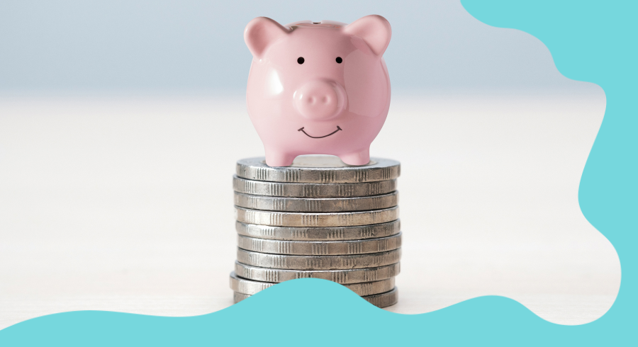 A very small piggy bank sat on top of a stash of silver coins. The piggy bank is pink and the pig is smiling.