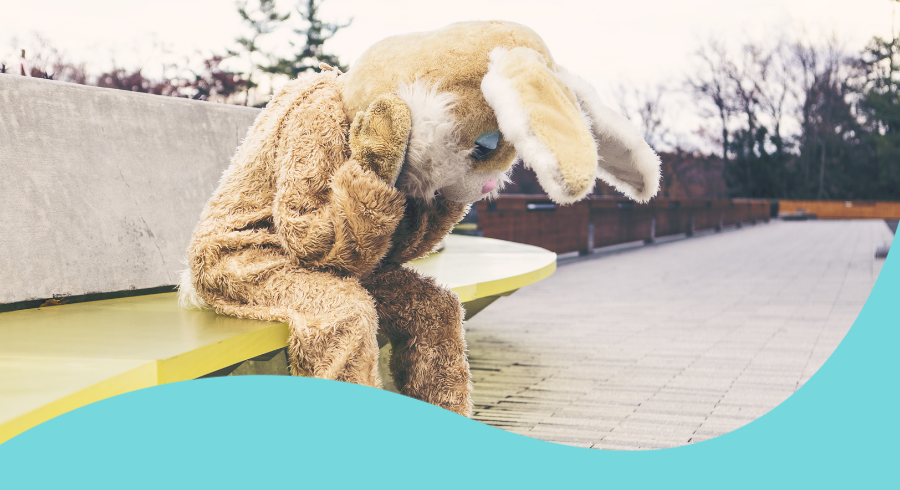 An image of a person dressed as a bunny rabbit looking glum with their head in their hands sat on a yellow bench.